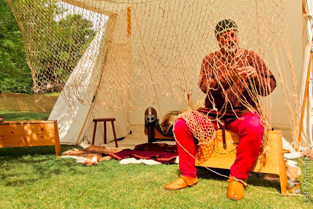 a man weaving a fishing net web